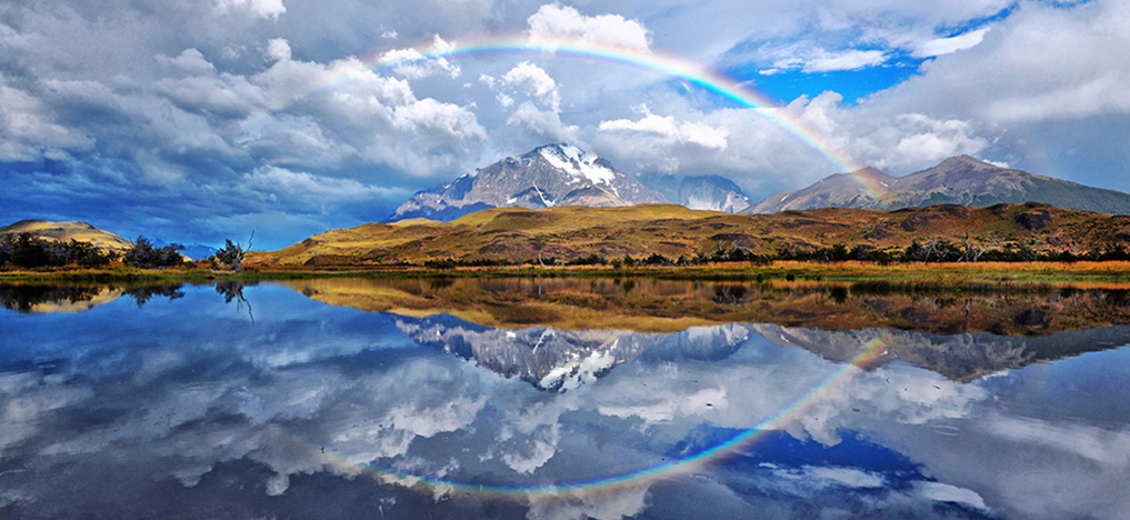 rainbow reflecting mountains and water