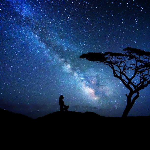 Silhouette of woman near a tree meditateing under the milky way galaxy